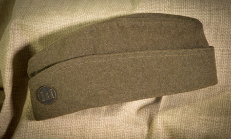 Overseas Hat — This hat was issued to American soldiers after they arrived in France. It was designed to fold and store easily in a pocket when a soldier needed to put on a helmet or gas mask. — Courtesy of Bob Ford